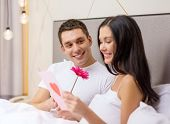 hotel, travel, relationships, holidays and happiness concept - smiling couple in bed with postcard and pink flower