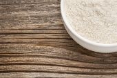gluten free brown rice flour - a ceramic bowl on grained wood background