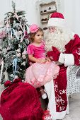 little girl in a beautiful dress sits on a lap at Saint Nicolas