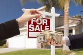 Agent Handing Over Keys as Buyer is Handing Over Cash for House with Home and For Sale Real Estate S