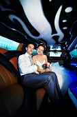 Happy Bride And Groom In Wedding Limo