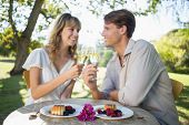 Cute happy couple sitting outside toasting with champagne with dessert on a sunny day