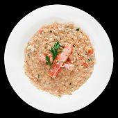 Risotto with crab meat and herbs, isolated on black