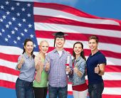 education and people concept - group of standing smiling students with diploma and corner-cap showing thumbs up