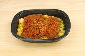 stock photo of biryani  - Convenience meal lamb biryani in a plastic tray on a wooden tabletop - JPG