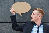Young business man holding empty speech bubble in front of a wall