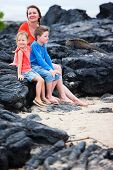Mother and kids looking at endemic marine iguana while on vacation at Galapagos islands