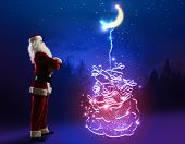 Santa Claus with big bag of gifts against night background