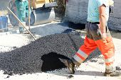 Men hard working on asphalting road