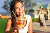 Woman drinking alcohol Mai Tai drink on Hawaii giving toast saying cheers looking at camera at beach club. Beautiful girl enjoying alcoholic beverage cocktail. Smiling happy woman on Hawaiian beach.