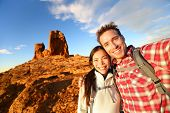 Selfie - Happy couple taking self portrait photo hiking. Two lovers or friends on hike smiling at ca