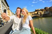 Happy couple selfie photo on travel in Florence. Romantic woman and man in love smiling happy taking