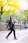 Fashion urban young woman living city lifestyle walking in leather jacket crossing streets in full l