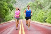 Running young multicultural couple exercising fitness outside on road in pretty nature jogging happy smiling. Asian female model and Caucasian male model training together.