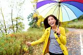Autumn woman happy in rain running with umbrella. Female model looking up at clearing sky joyful on