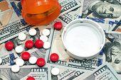 Pills and Pill Bottle On Hundred Dollar Bills
