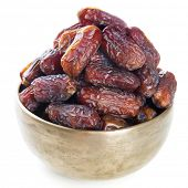 Dried date palm fruits or kurma, ramadan food which eaten in fasting month. Pile of fresh dried date fruits in golden metal bowl isolated on white background.