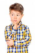 Cute 7 years old boy standing and thinking about something. Isolated over white.