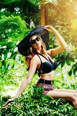 Beautiful young woman  among the tropical plants. Vacation. Tropics. Fashion shot.