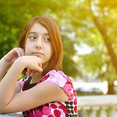 Young girl alone in park, face close up. Toned.