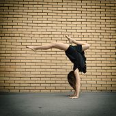 Attractive teen girl dancing outdoor against bricks wall. Toned.