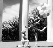 Elegant beautiful teen girl dancer in pointes posing outdoor with little boy holding colored balloon