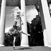 Attractive teen girl dancing outdoor in park against columns with balloons. Black and white.