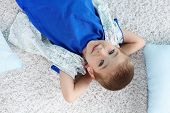 Cute kid lying on the floor with his hands behind his head