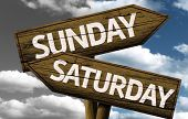 Time concept on wooden sign, Sunday x Saturday