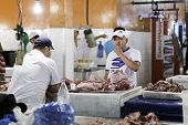 MANAUS, BRAZIL - CIRCA FEB 2014: A butcher at a meat counter in Mercado Municipal Adolfo Lisboa in Manaus, Brazil