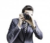 Male photographer focusing and composing an image with his professional digital SLR camera pointing the lens directly at the viewer on white background