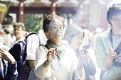 TOKYO, JAPAN - CIRCA MAY 2014: People pray at Senso-ji Temple in Tokyo,Japan. The Senso-ji Temple is the symbol of Asakusa and one of the most famed temples in Japan.