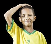 Brazilian little boy putting his hand on his head on black background