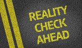 Reality Check Ahead written on the road