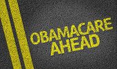 foto of mandate  - Obamacare Ahead written on the road - JPG