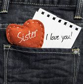 Sister I love you! written on a peace of paper and a heart on a jeans background