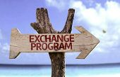 Exchange Program wooden sign with a beach on background