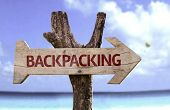 Backpacking wooden sign with a beach on background
