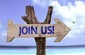 Join Us! wooden sign with a beach on background