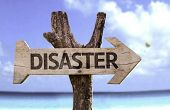 Disaster wooden sign with a beach on background