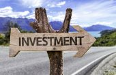 Investment wooden sign with a street on background