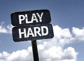 Play Hard sign with clouds and sky background