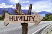 Humility wooden sign with a street on background