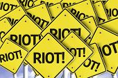 Riot! written on multiple road sign