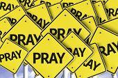 Pray written on multiple road sign