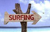 Surfing wooden sign with a beach on background