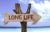 Long Life wooden sign with a beach on background