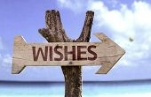 Wishes wooden sign with a beach on background
