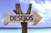 Wishes (In Portuguese) wooden sign with a beach on background