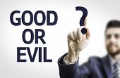 Business man pointing to transparent board with text: Good or Evil?